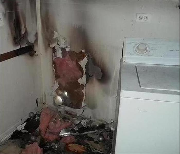 laundry room in house with fire damaged wall around dryer vent