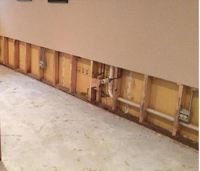 Wall with demolition flood cut on lower two feet, no drywall and no carpet