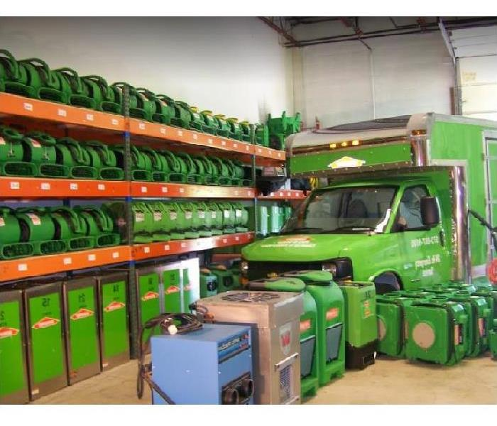 Inside of SERVPRO facility; SERVPRO restoration equipment stacked along wall and SERVPRO vehicle